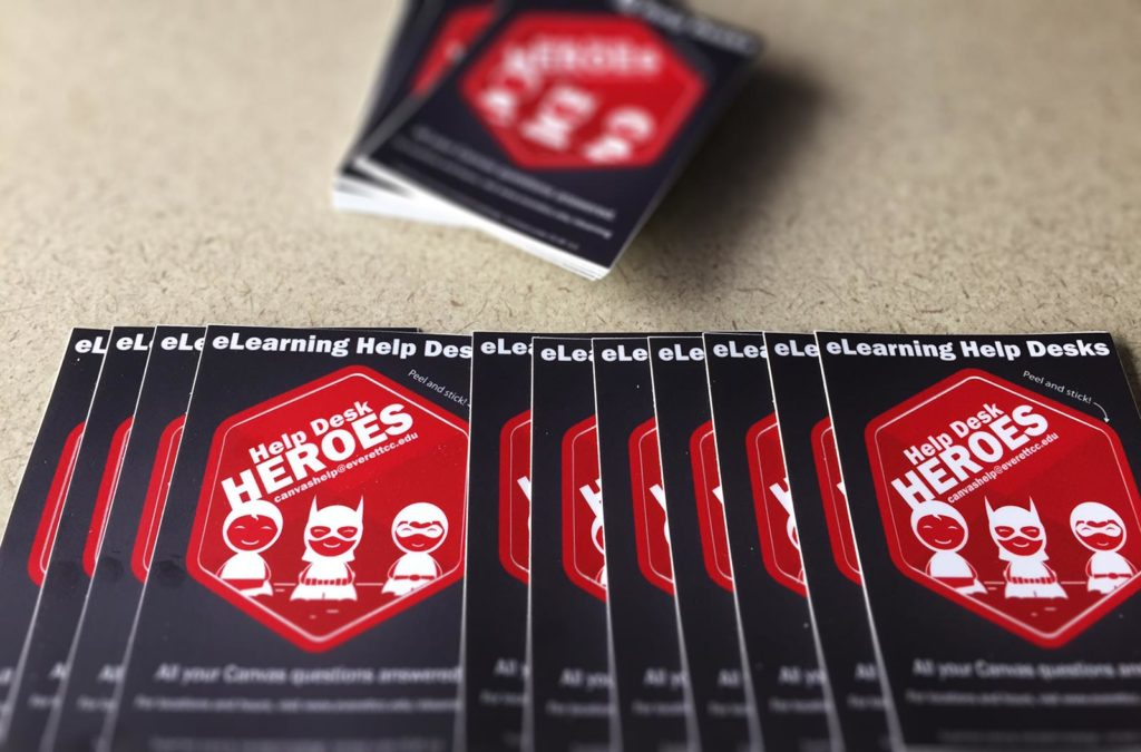 2017 eLearning Help Desk stickers displayed on a table. The sticker is a red hexagon with three cartoon superheros, accompanied by the text 'Help Desk Heroes'