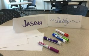 Two table name tags, one with the name 'Jason' and one with the name 'Debby' written on them. In the foreground are several blank sheets of paper and five markers.