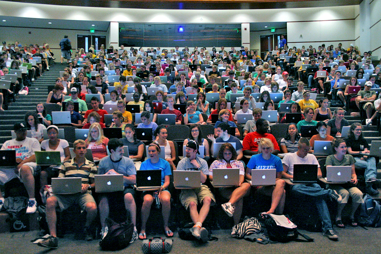 Students sit in a large lecture hall, each with a laptop