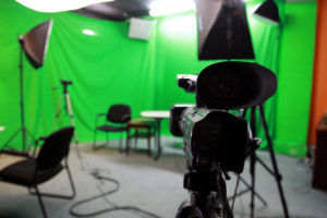 Video studio with green screen, lights, and video camera in foreground