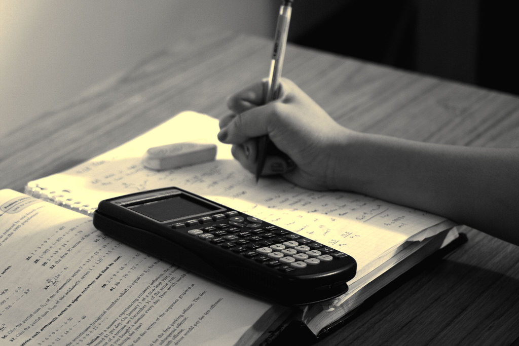 Student studying -- a calculator, textbook, notebook, and a hand holding a pen